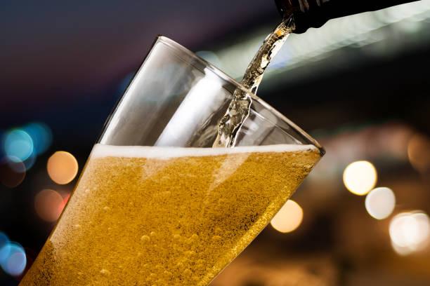 ピンぼけ光夜背景にガラス瓶から注ぐビールの動き - ビール ストックフォトと画像