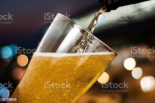 Motion Of Beer Pouring From Bottle Into Glass On Bokeh Light Night Background — стоковые фотографии и другие картинки Алкоголь - напиток