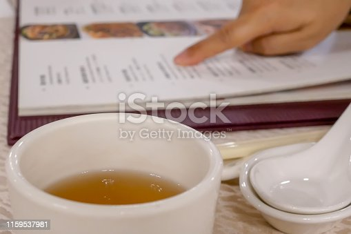 Motion of woman looking at menu inside Chinese restaurant