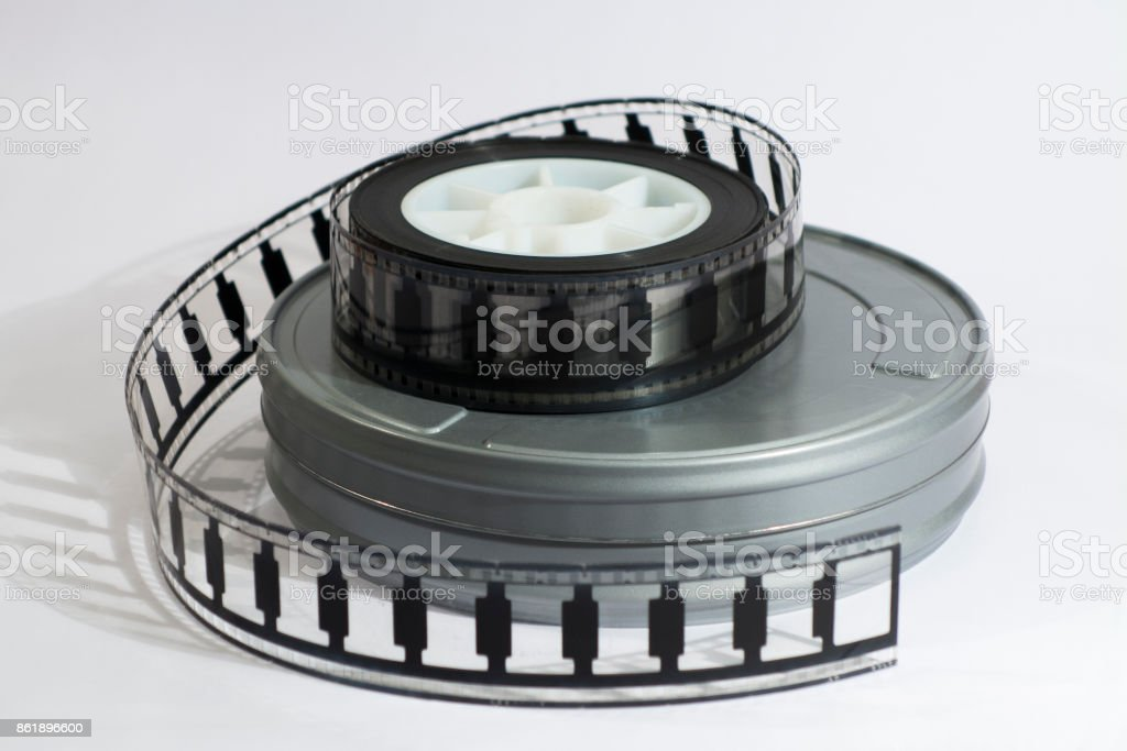Motion picture film roll lying on top of a film canister. stock photo