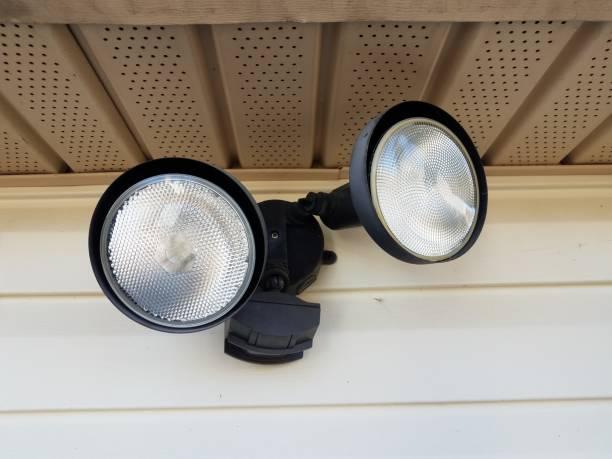 motion sensor flood light on white home siding stock photo