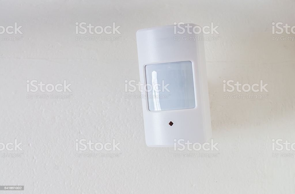 Motion sensor or detector for security system mounted on wall. stock photo