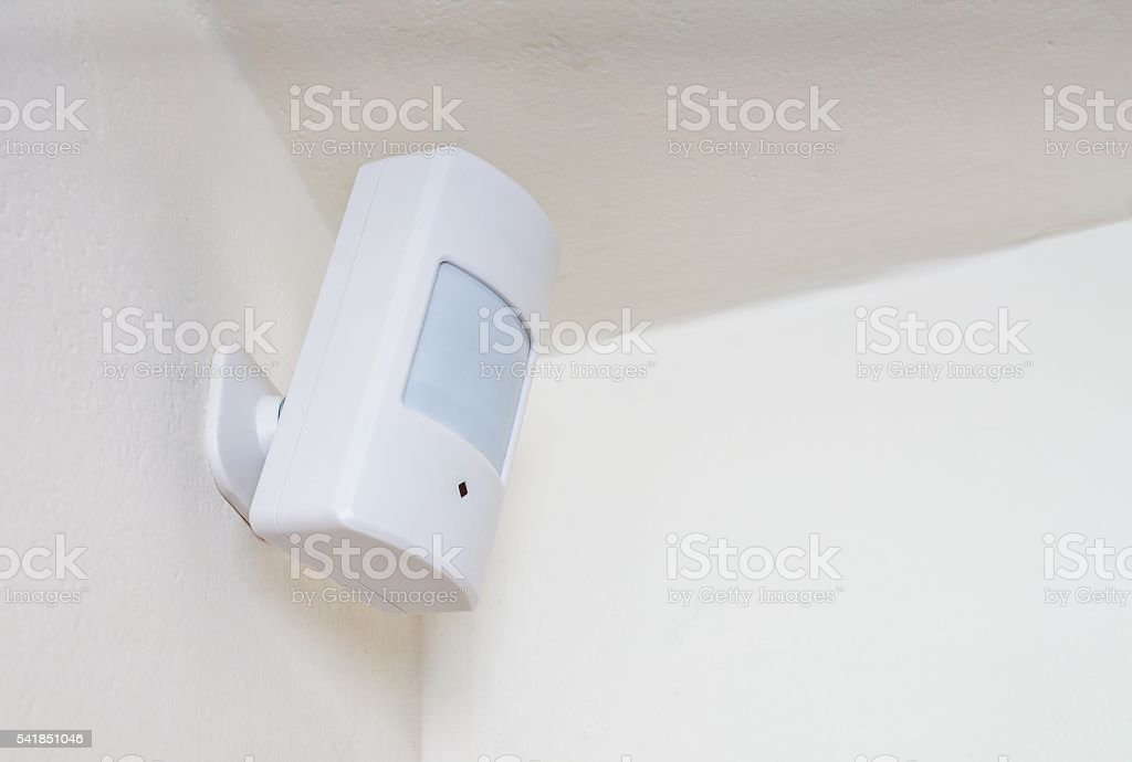 Motion sensor or detector for security system mounted on wall. - foto stock