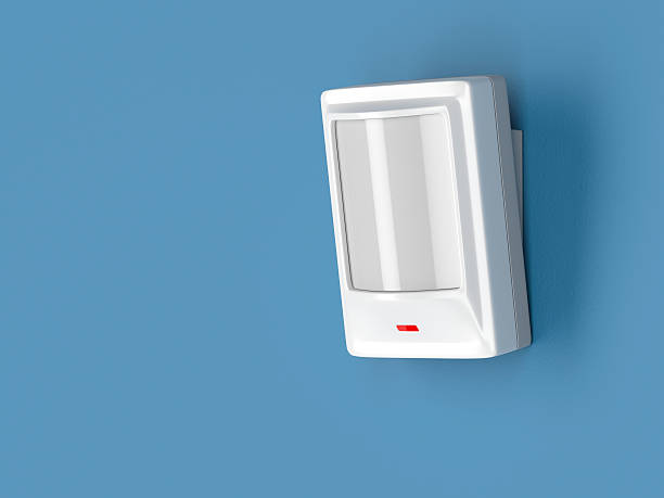 Motion sensor Motion detector attached on blue wall sensor stock pictures, royalty-free photos & images