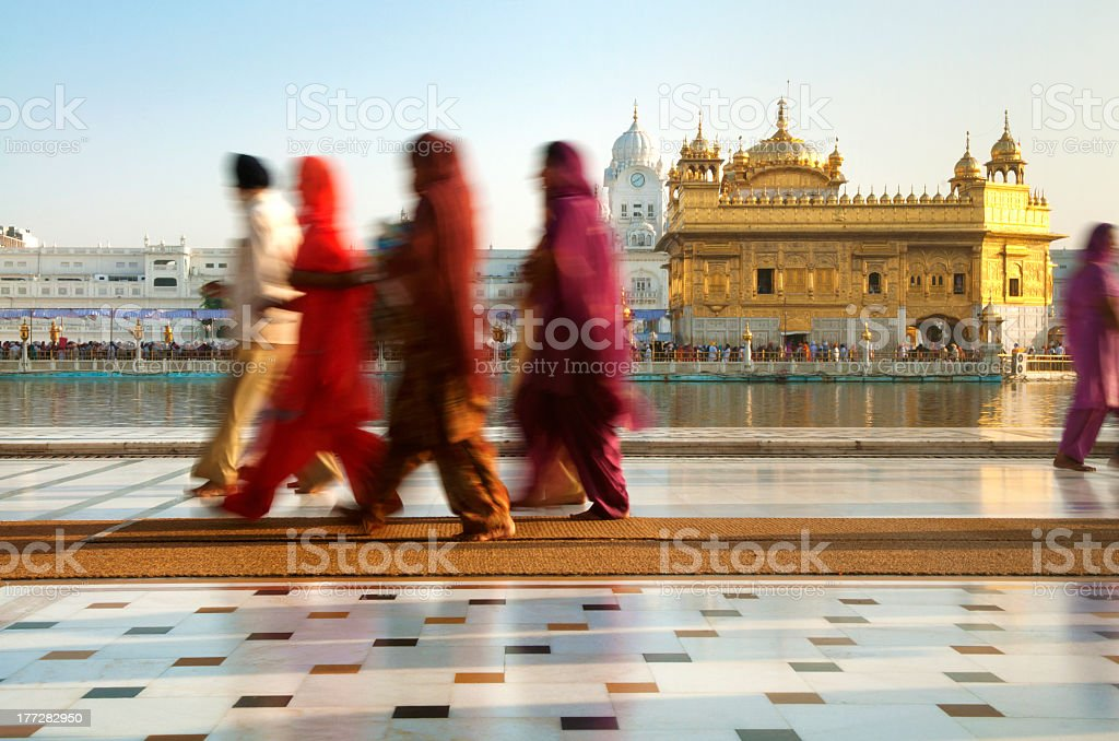 Motion-blurred men walking on the grounds of Indian temple stock photo