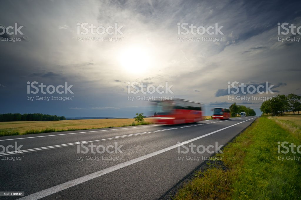 Motion-blurred red buses traveling on the asphalt road between cornfields in the countryside under the sun shining through dramatic clouds before the storm stock photo