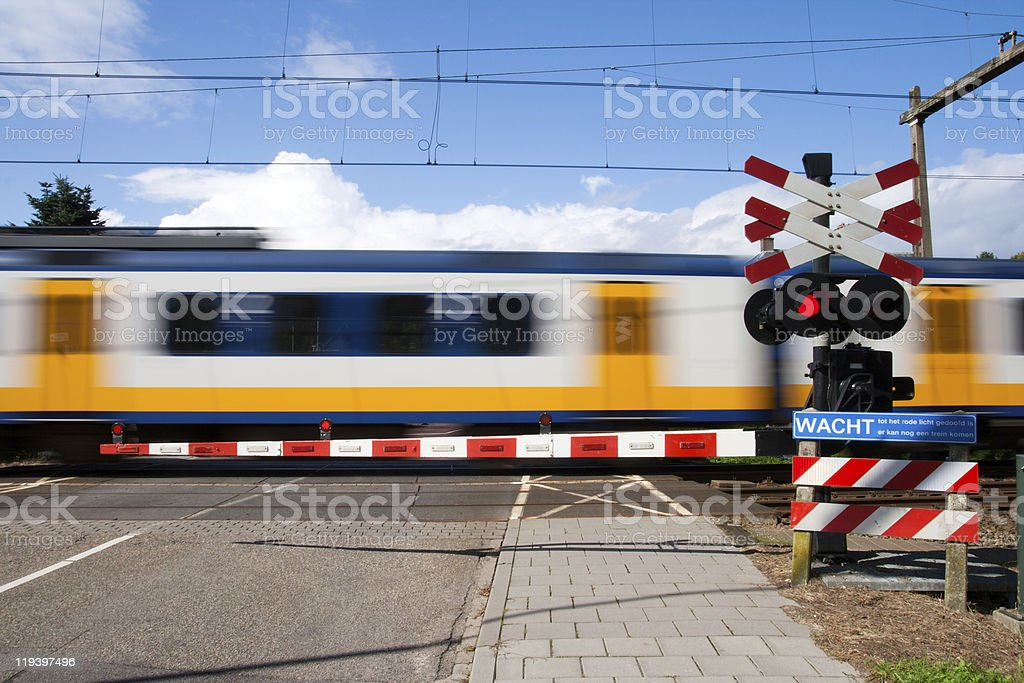 Motion-blurred train passing by a railroad crossing stock photo
