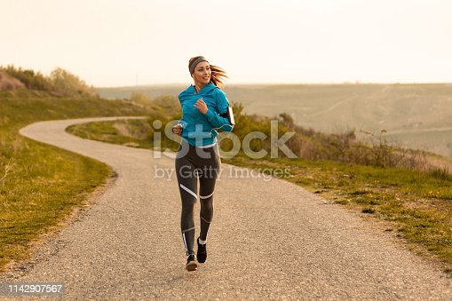 Young female runner jogging on the road at dawn. Copy space.
