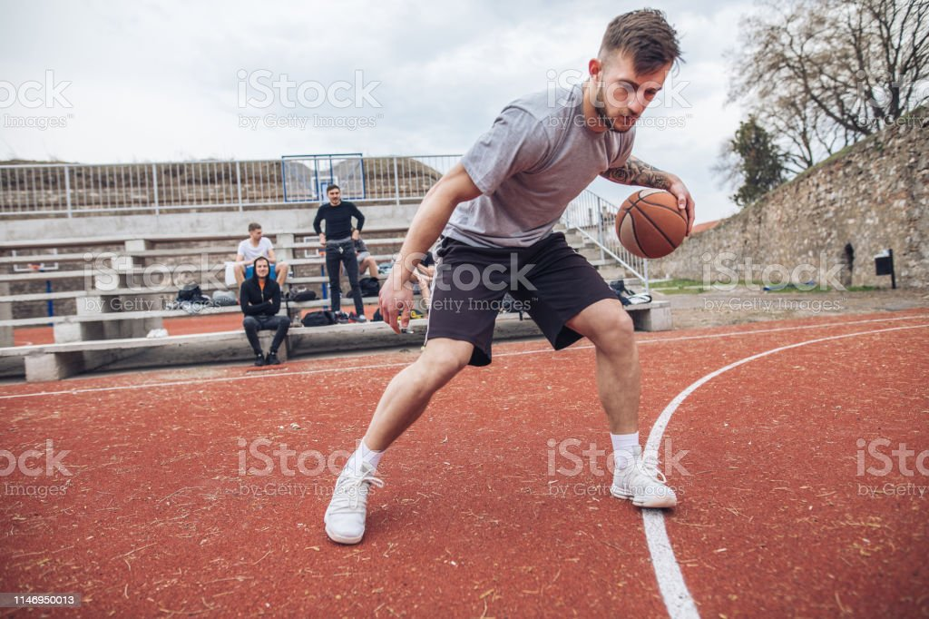 Handsome and healthy living man dribbling with a ball on a sports...