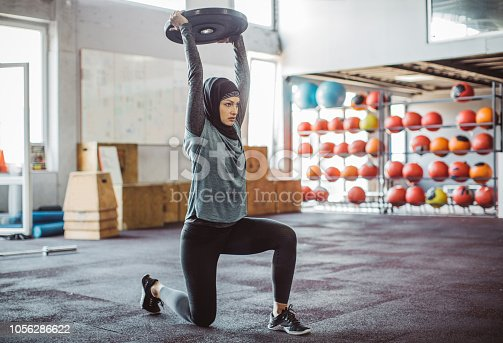Young woman on cross training exercising. Wearing sports clothing and hijab.