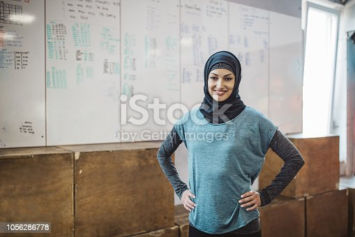 Young woman on cross training. Preparing for exercising. Wearing sports clothing and hijab.