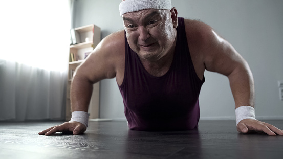 Motivated plump man in his 50s doing push-up with great effort, home training, stock footage