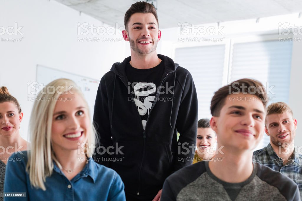 Motivated university friends listening in therapy Smiling friends at lecture hall. Male and female students are listening in group therapy. They are motivated. 18-19 Years Stock Photo