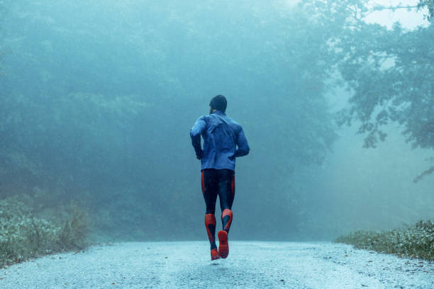 Motivated young man running in the rain