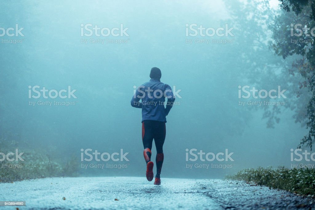 Motivated young man running in the rain. stock photo