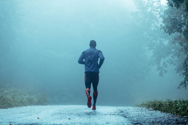 Motivated young man running in the rain. Motivated young man running in the rain. Rear view. Copy space. running stock pictures, royalty-free photos & images