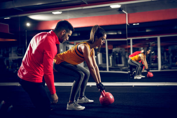 motivated young sporty female trying to lift weight with a assistance of her coach. - training imagens e fotografias de stock