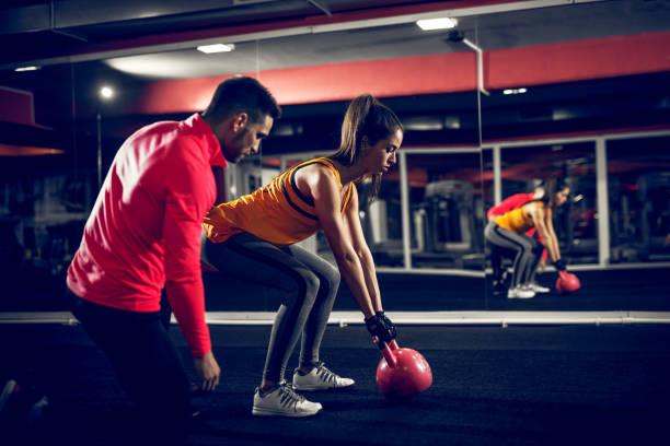 gemotiveerde jonge sportieve vrouw probeert om gewicht te heffen met een hulp van haar coach. - personal trainer stockfoto's en -beelden