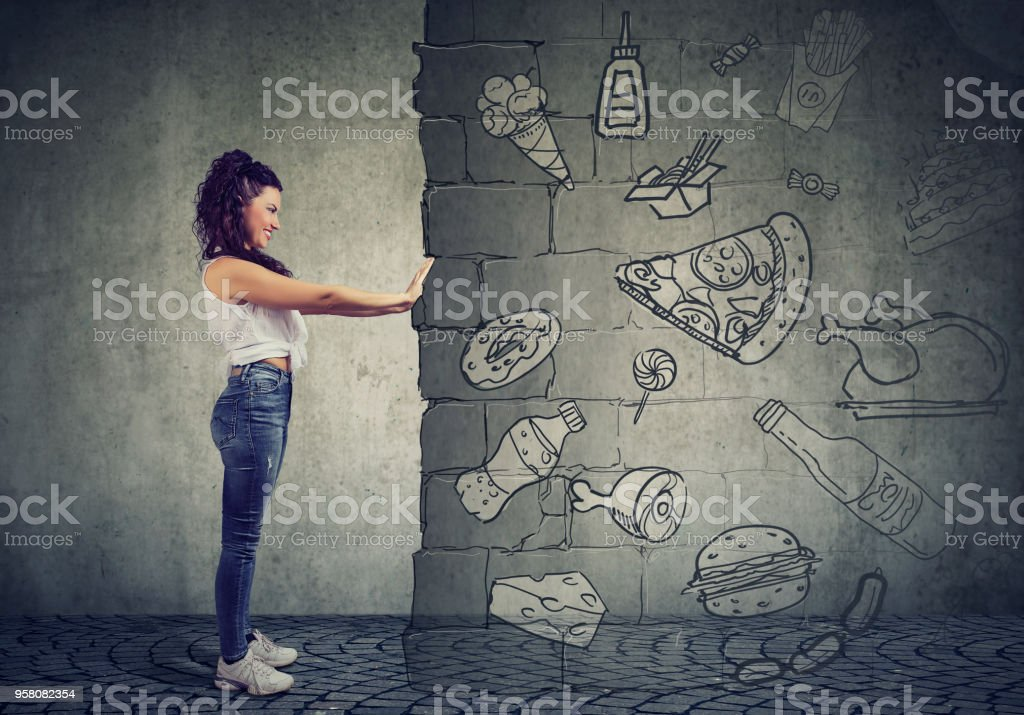 motivated young woman resisting temptation of eating fast foot and choosing better diet. stock photo