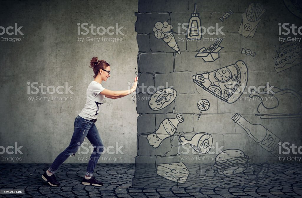 motivated young woman resisting temptation of eating fast foot and choosing better diet stock photo