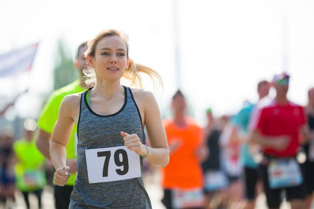motivierte junge frau läuft marathon - joggerin stock-fotos und bilder