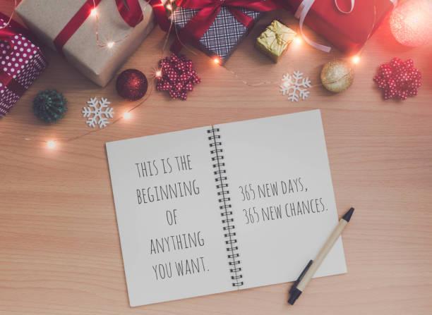 motivation und inspiration zitat auf notizbuch und stift mit weihnachten und neujahr urlaub geschenk-box mit dekorativen ornamenten auf holztisch. geschenke und glückwünsche konzept. - zitate weihnachten stock-fotos und bilder