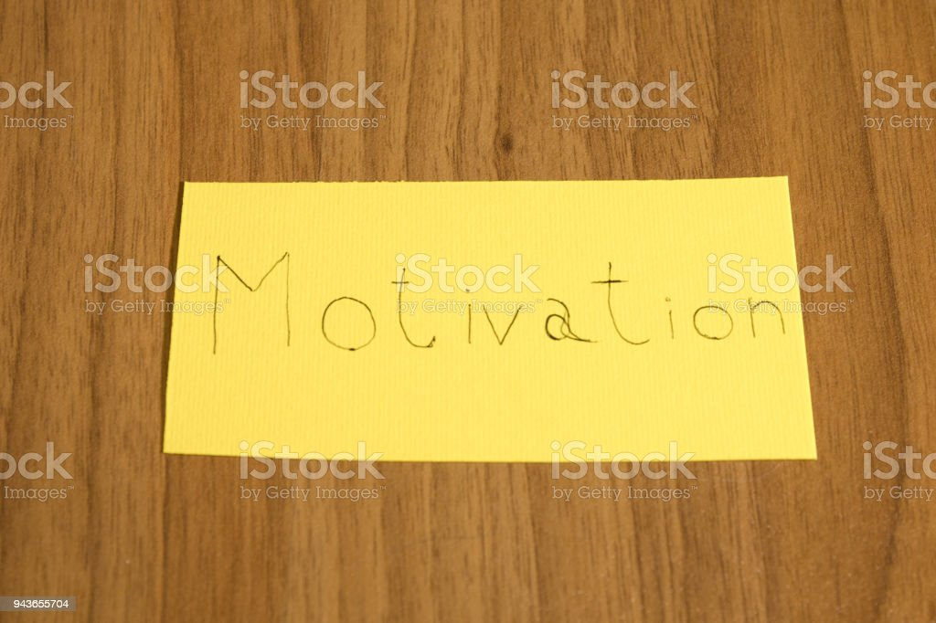 Motivation handwrite on a yellow paper with a pen on a table composition stock photo