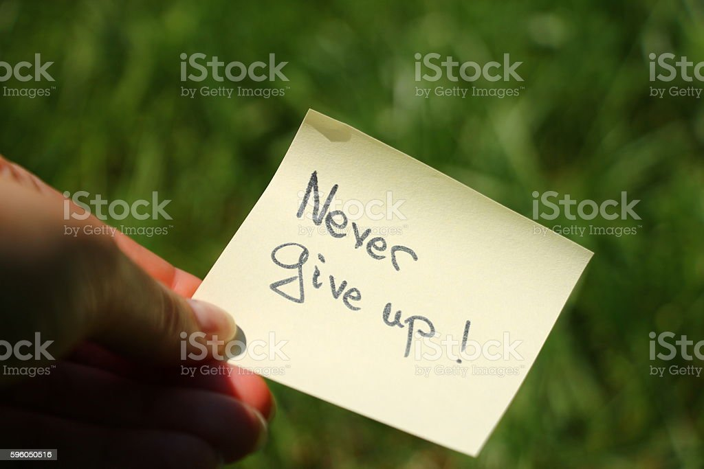 Motivation message Never give up in woman's hand royalty-free stock photo