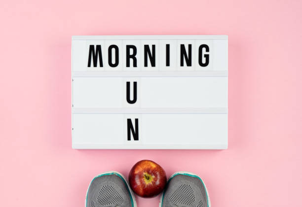 Motivation quotes on light box, apple and sport shoes on the pink stock photo