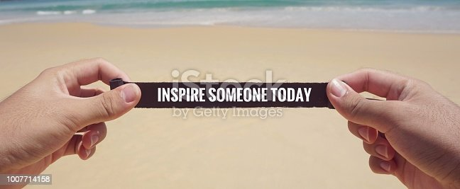 'Inspire someone today' written on a piece of paper. With vintage styled background.
