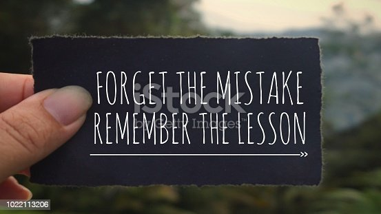 'Forget the mistake, remember the lesson' written on a black paper. Vintage styled background.