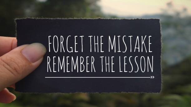 Motivational and inspirational quote. 'Forget the mistake, remember the lesson' written on a black paper. Vintage styled background. mistake stock pictures, royalty-free photos & images