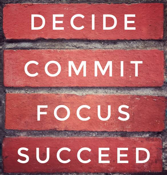 Motivational and inspirational quote. 'DECIDE, COMMIT, FOCUS, SUCCEED' written on red brick wall. Vintage styled background. dedication stock pictures, royalty-free photos & images