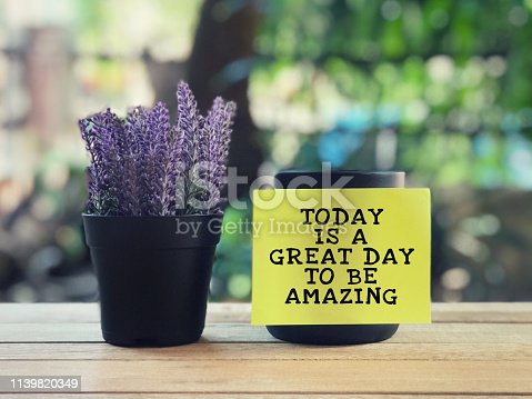 Today Is A Great Day To Be Amazing written on a yellow sticky paper. Blurred styled background.