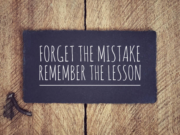 Motivational and inspirational quote. 'Forget the mistake, remember the lesson' written on a black piece of paper with background of wooden wall. mistake stock pictures, royalty-free photos & images