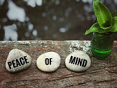 'Peace of mind' written on white pebbles. With blurred vintage styled background.