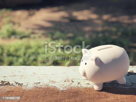 A piggy bank placed on a wooden table.