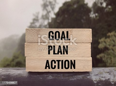 Goal, Plan, Action written on wooden blocks.