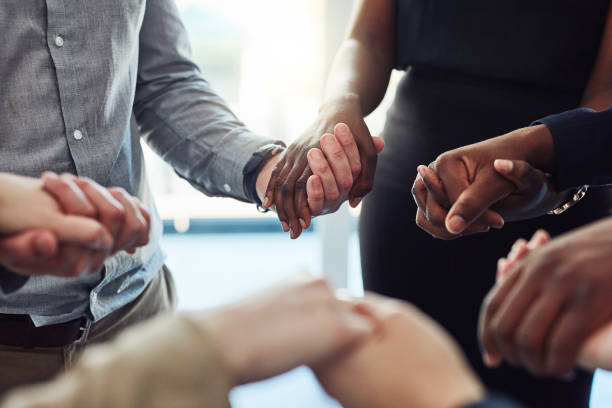 Motivational huddles aren't just for sports teams Cropped shot of a group of businesspeople standing together and holding hands in a modern office religion stock pictures, royalty-free photos & images