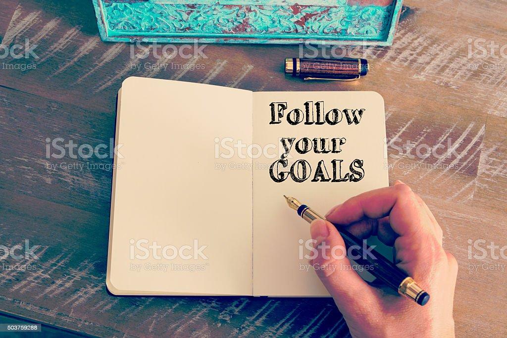 Motivational message FOLLOW YOUR GOALS written on notebook stock photo