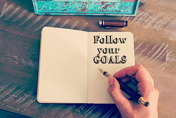 motivierende botschaft folgen sie ihre ziele schreiben auf notebook - intelligente zitate stock-fotos und bilder