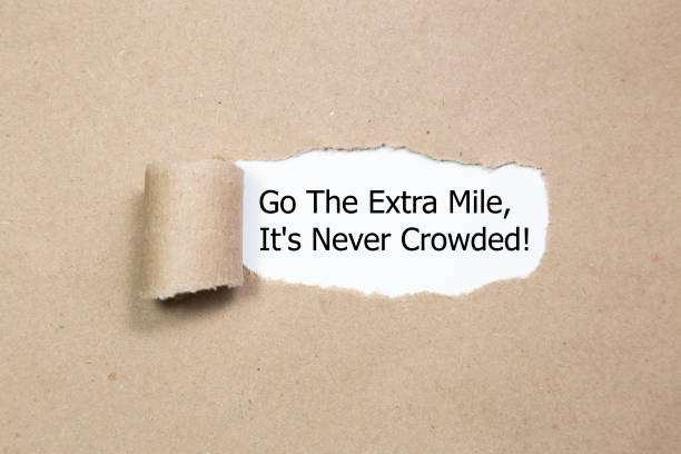 Motivational quote Go The Extra Mile It's Never Crowded appearing behind ripped paper. stock photo