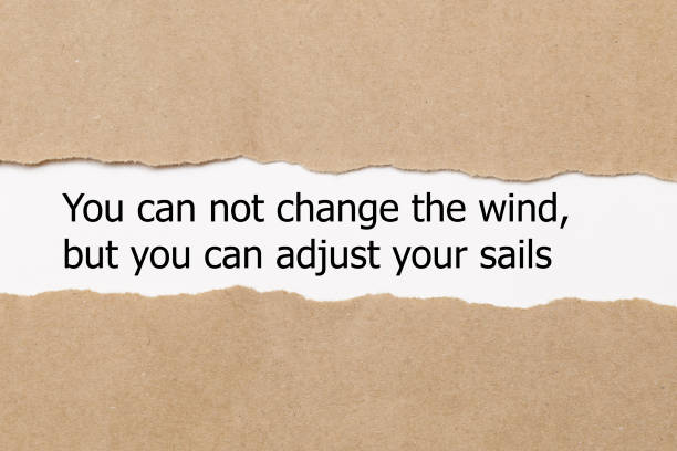 Motivational quote You can not change the wind but you can adjust your sails, appearing behind torn paper. stock photo