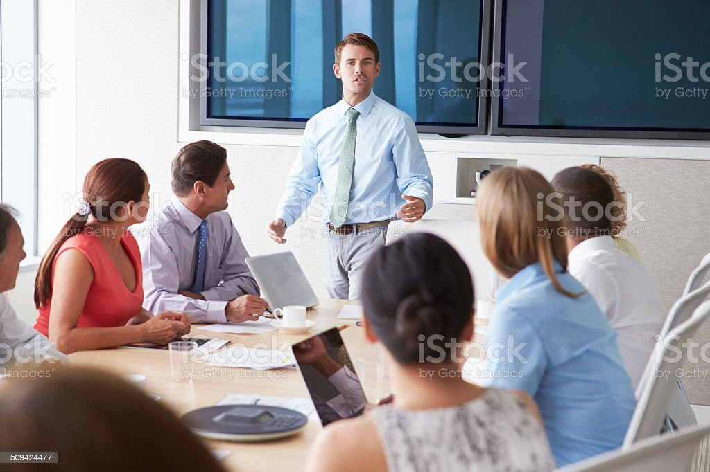 Motivational Speaker Talking To Businesspeople In Boardroom Motivational Speaker Talking To Businesspeople In Boardroom Sitting Around Table Listening 20-29 Years Stock Photo