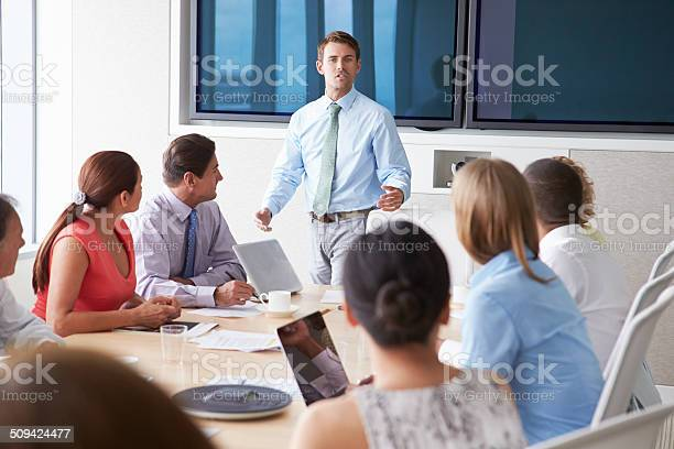 Motivational Speaker Talking To Businesspeople In Boardroom Stock Photo - Download Image Now