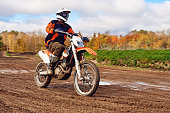 istock Motocross, enduro rider on dirt track. The forest behind him 690653762