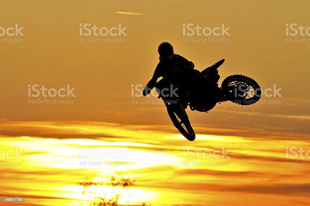 Motocross jump into the sunset stock photo