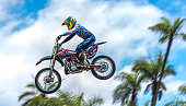 Sao Paulo, Sao Paulo, Brazil - December 3, 2017: Young doing outdoor maneuvers at event in Sao Paulo Brazil, flying in the air with his motocross motorcycle to the blue sky with effects of blurred and panning and blur