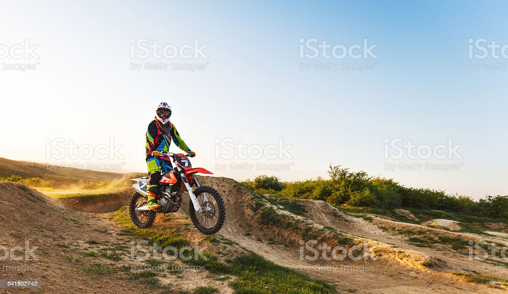 Motocross racer riding on dirt road and looking at camera. stock photo