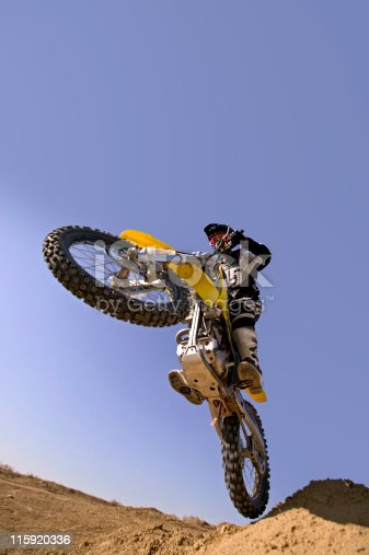 Motocross Rider Flying Over against Blue Sky